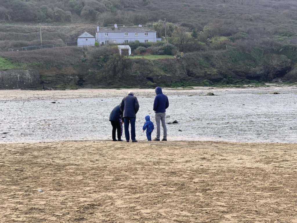 Family wrapped up on Mawgan Porth beach