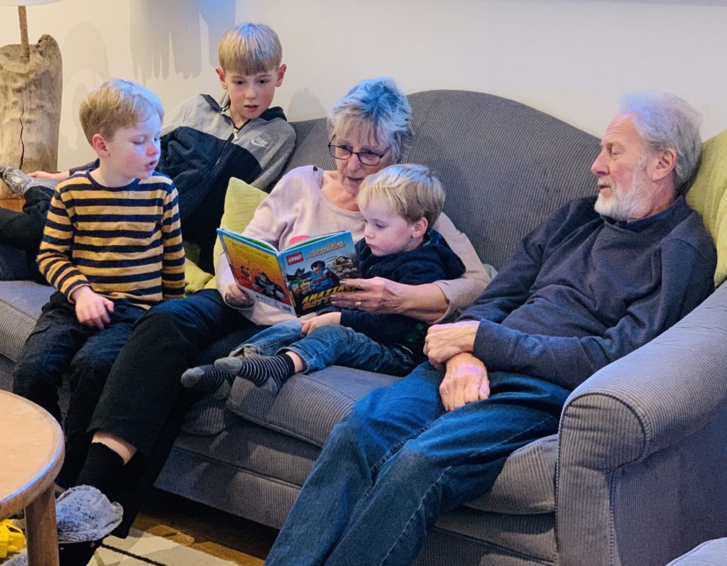 Cousins listening to a book with grandparents