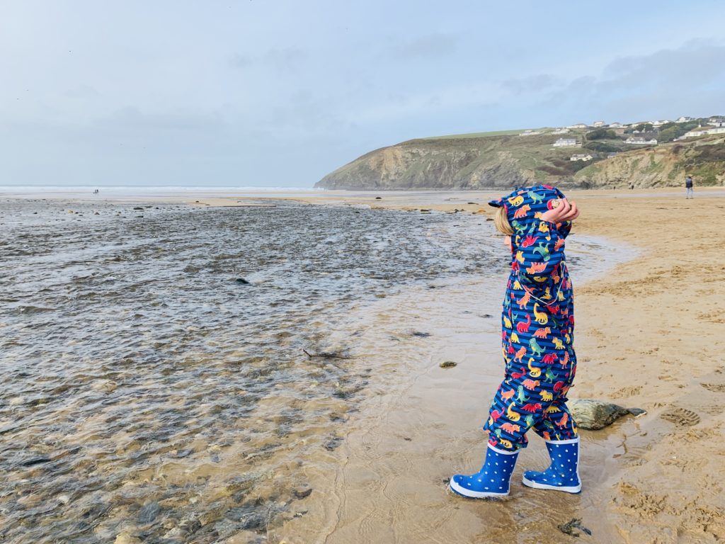 Toddler in puddle suits on Mawgan Porth beach