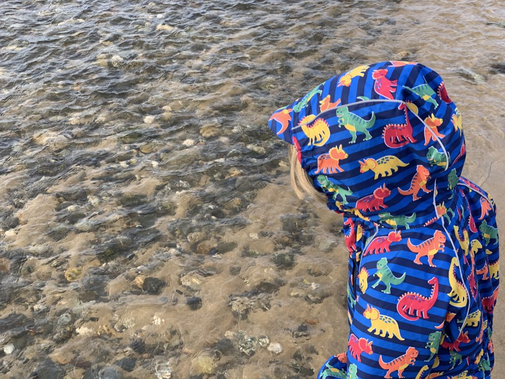Toddler throwing pebbles into a steam on Mawgan Porth beach
