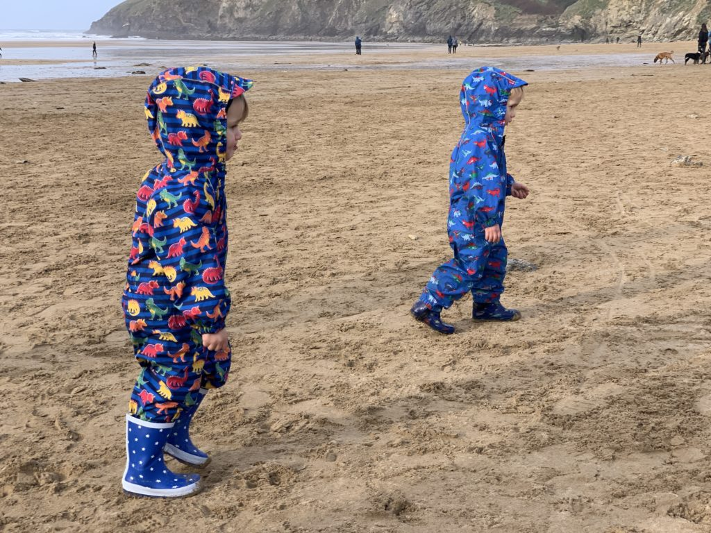 Toddlers in puddle suits on Mawgan Porth beach