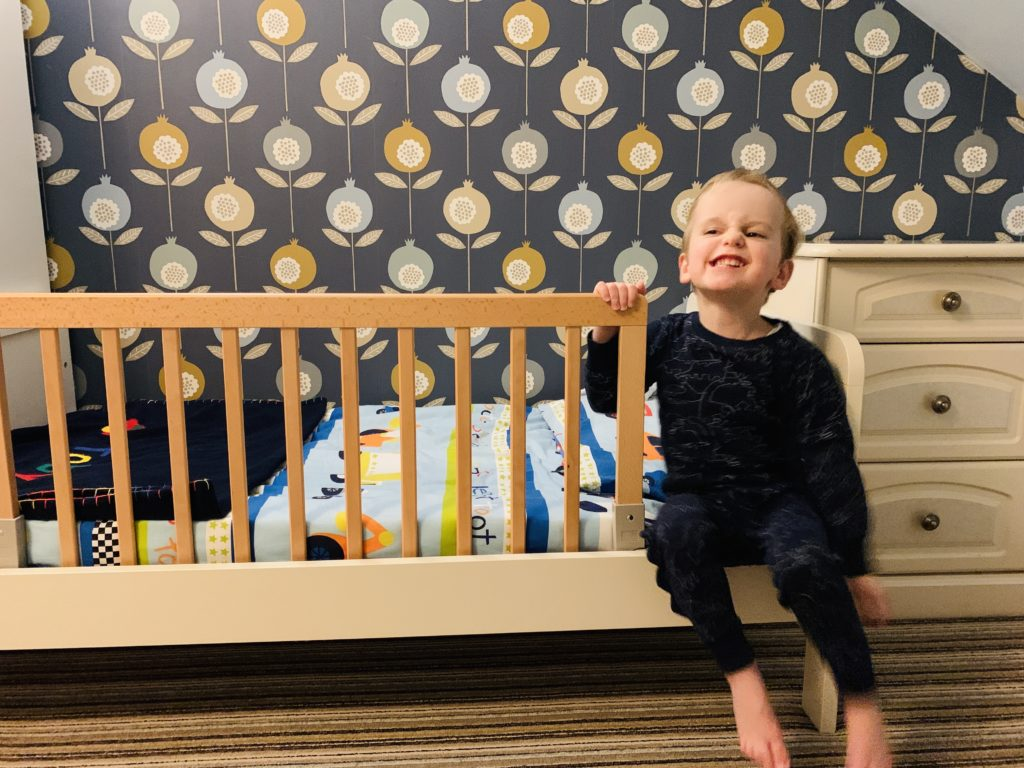 Toddler on the edge of his bed with a Baby Dan rail
