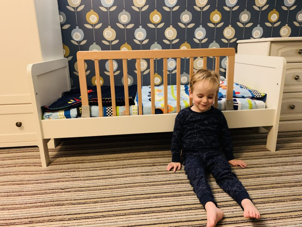 Toddler boy on the floor next to his new bed