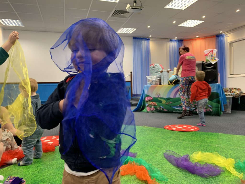 Toddler plays with a chiffon scarf at a baby group