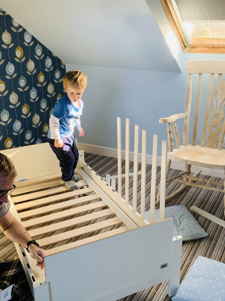 Toddler helping daddy build new beds