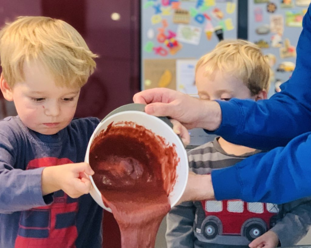 Twin toddlers making a red velvet cake