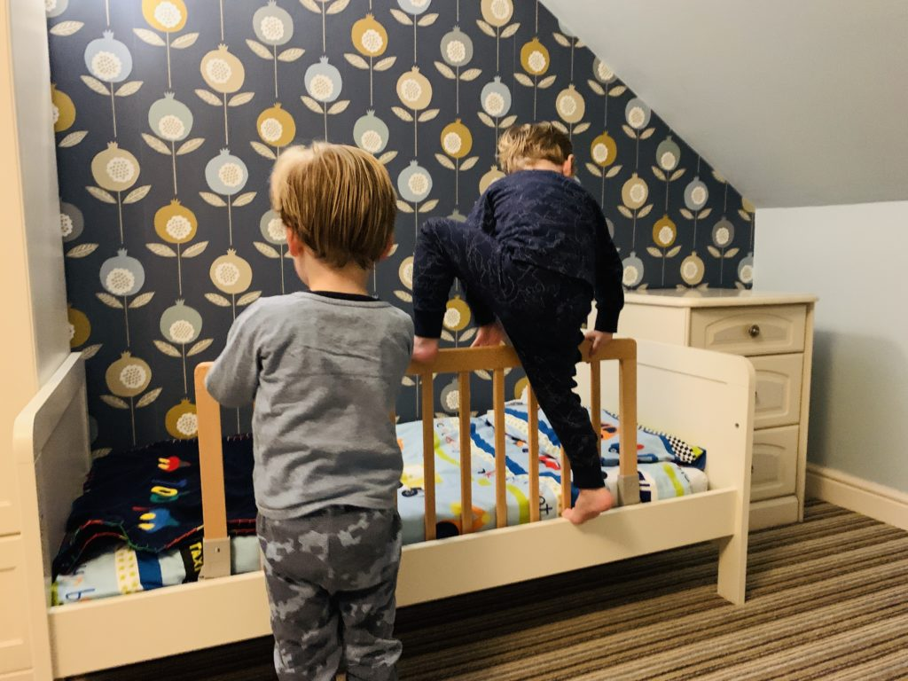 Twins climbing over bed rails