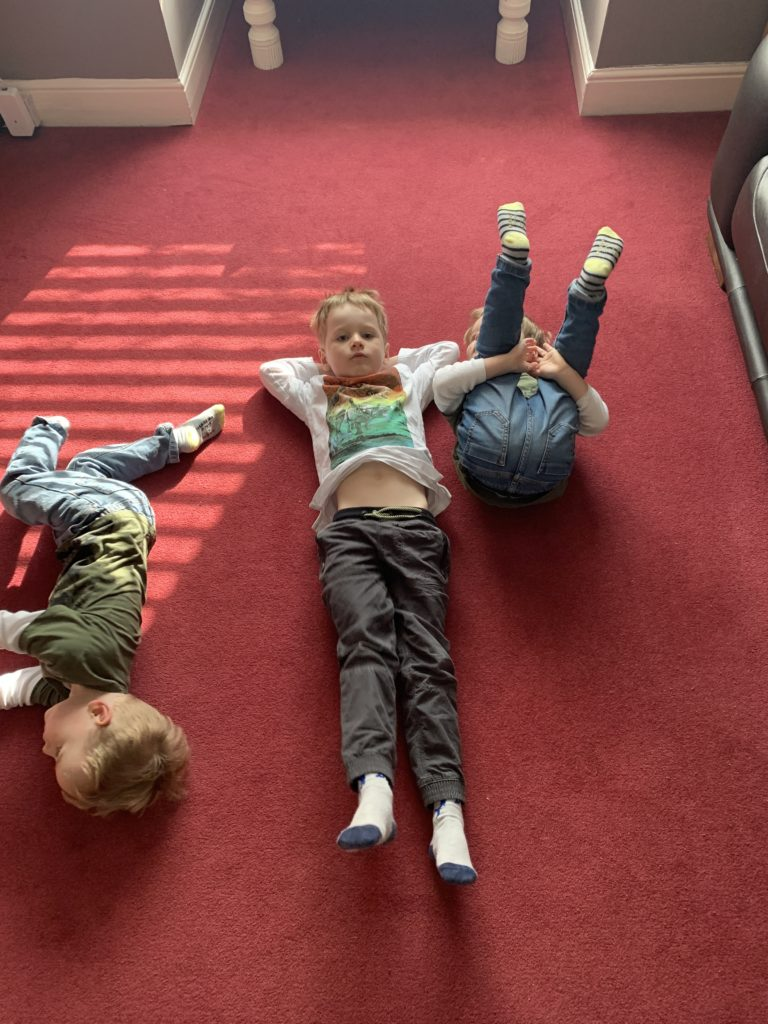 Twin toddlers and their four year old brother lie on the lounge floor