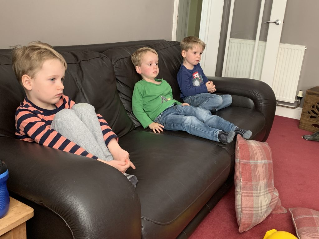 Two year old twin boys and four year old brother sit on settee watching tv