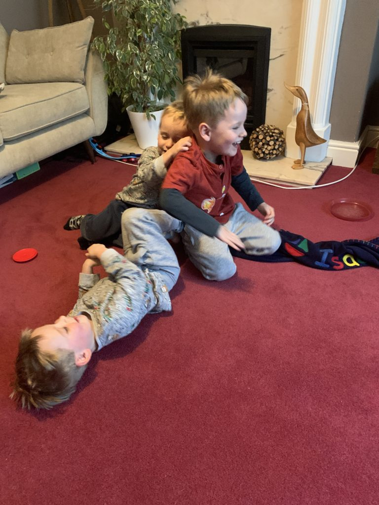 Twin toddlers and their brother play on the carpet