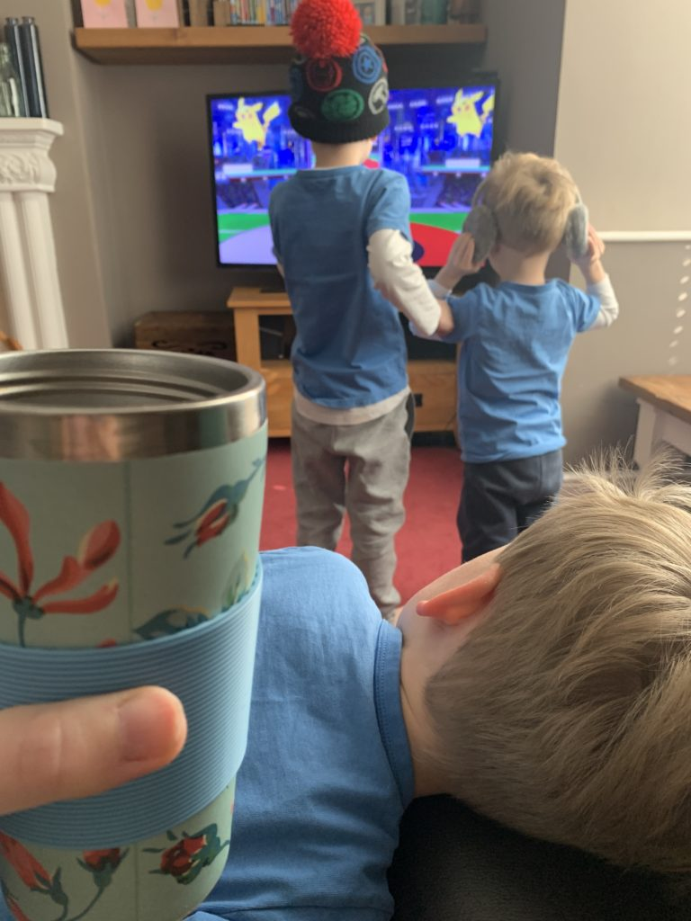 Toddler lies on mummy's laugh, whilst she drinks coffee from a travel mug and her other little boys do cosmic yoga in front of the tv