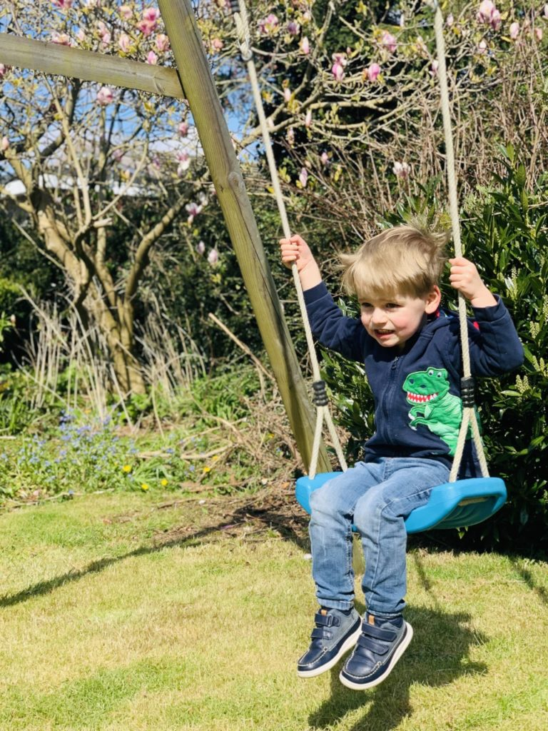 Toddler plays on a swing in the garden