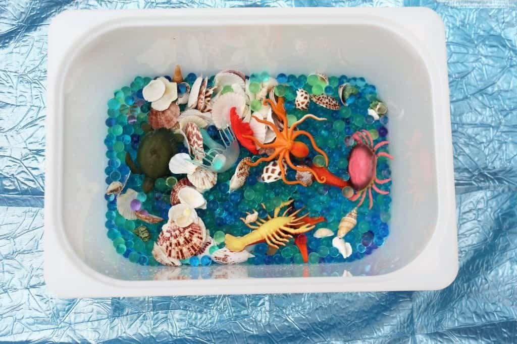 Toy box of ocean sensory play items to keep toddlers entertained at home