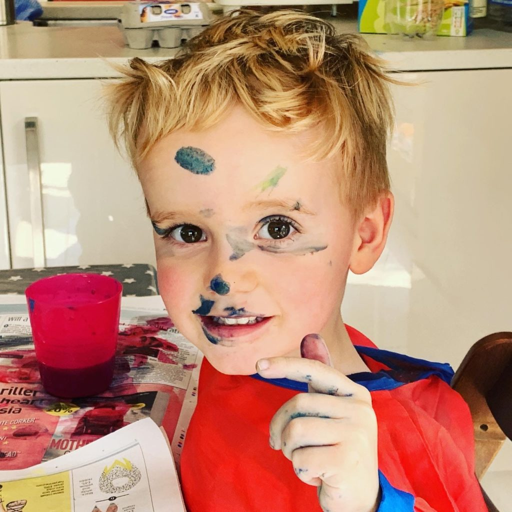 Toddler painting his face during lockdown