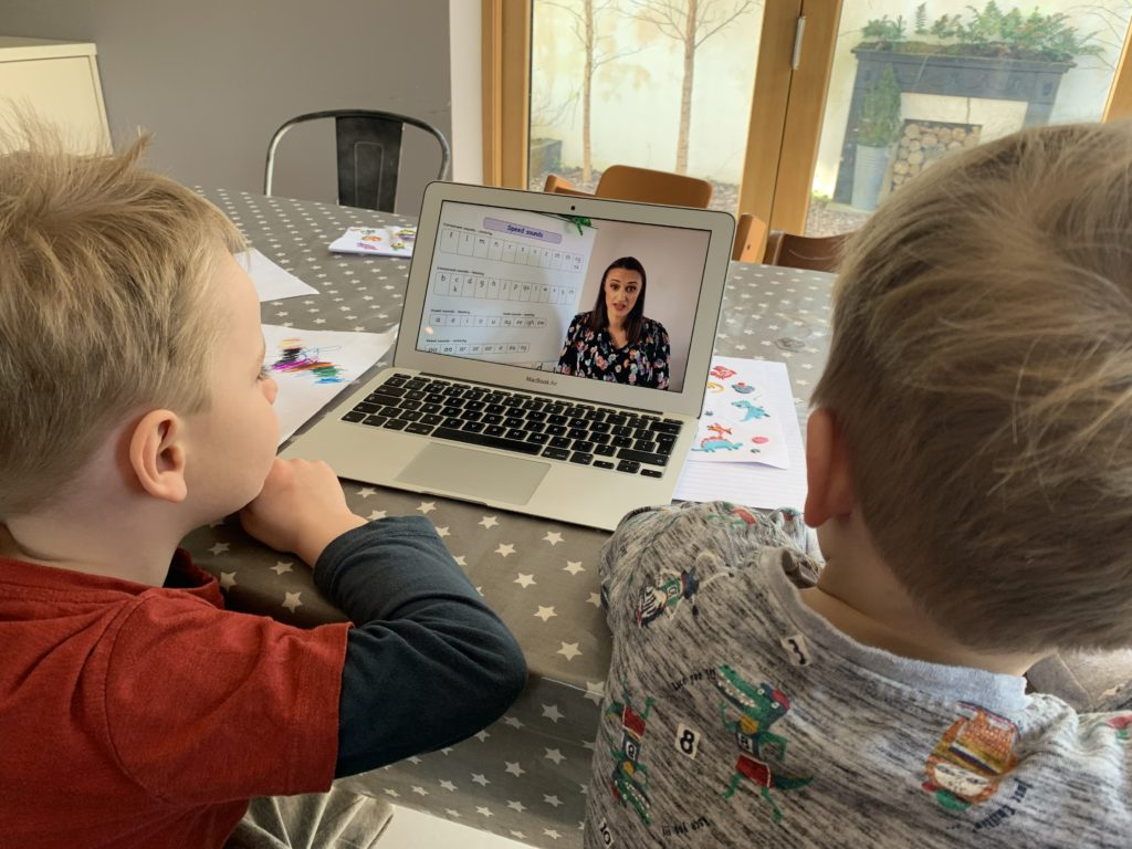 Four year old and two year old brothers watch a phonics You Tube video on a laptop