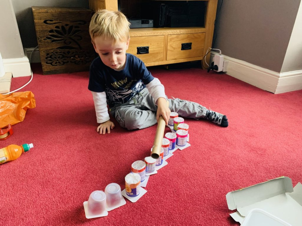 Toddler doing some junk modelling with yoghurt pots in a bid to keep toddlers entertained at home