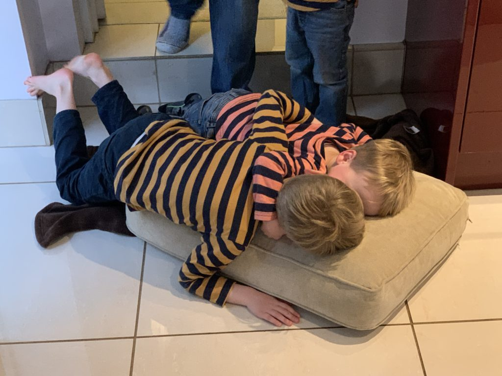 Twin toddlers bring sofa cushion into the kitchen to lie on the floor