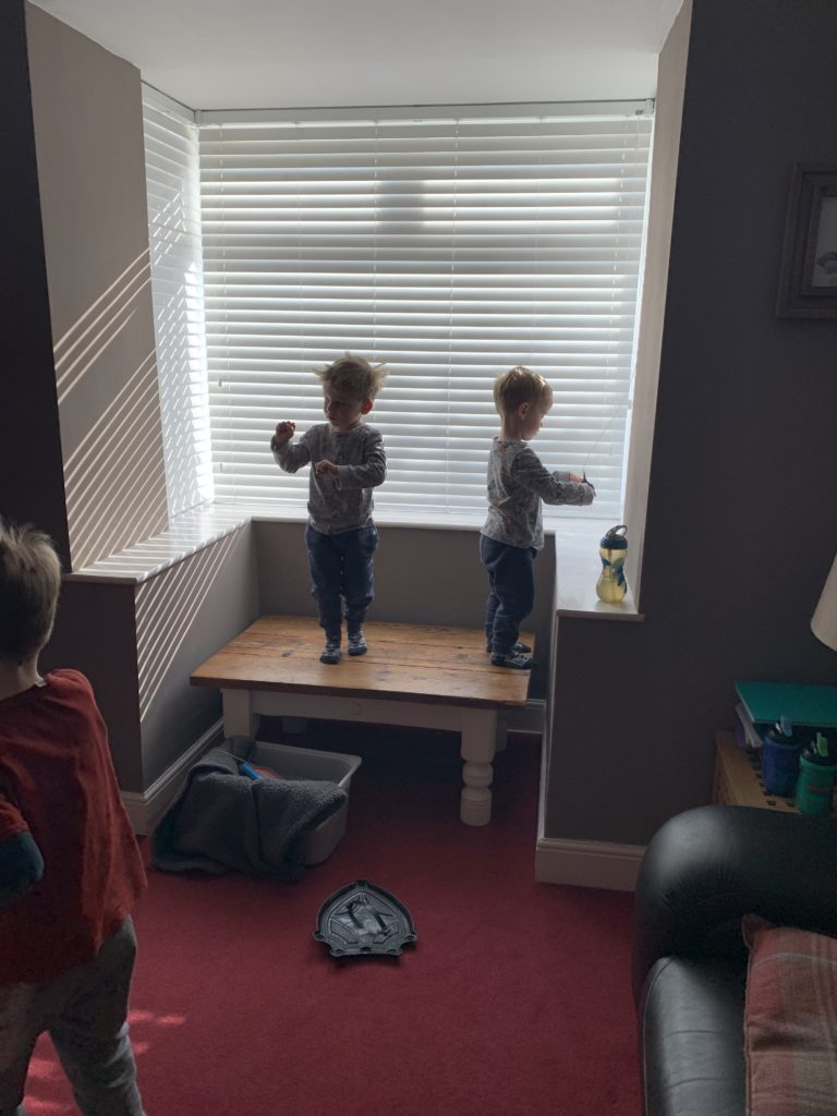 Twin toddlers stand on the coffee table