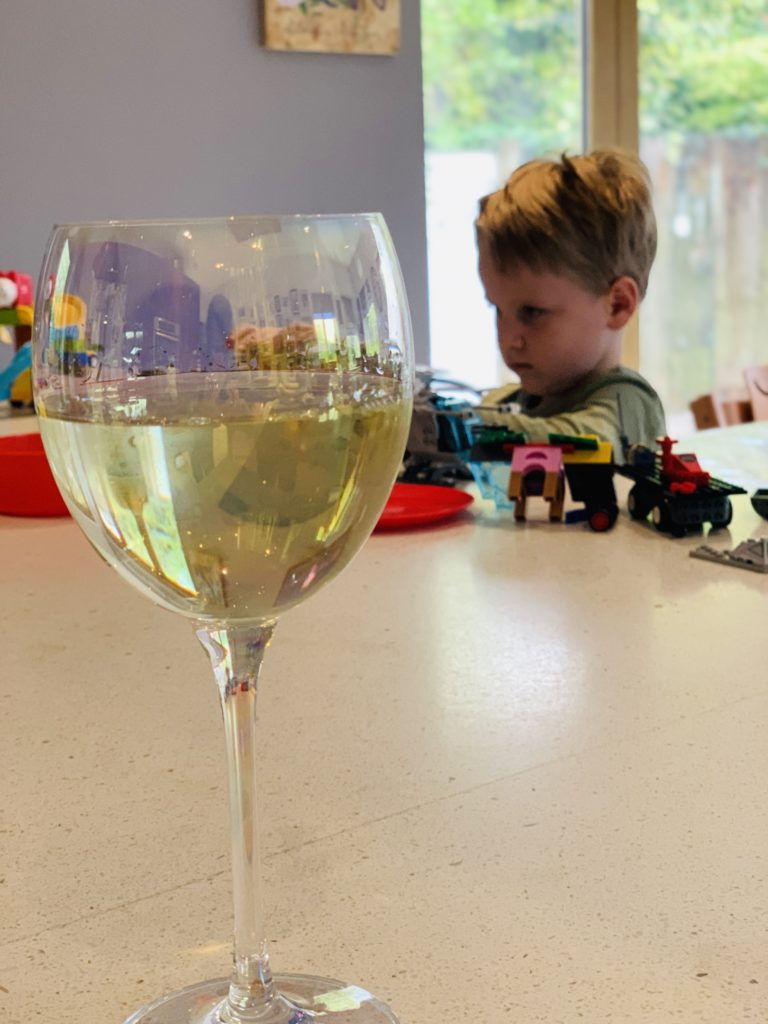 Wine on the kitchen worktop whilst four year old plays lego