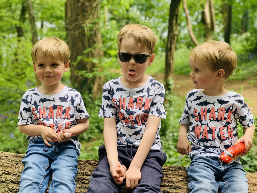 Four year old looking stroppy with his brothers in the woods