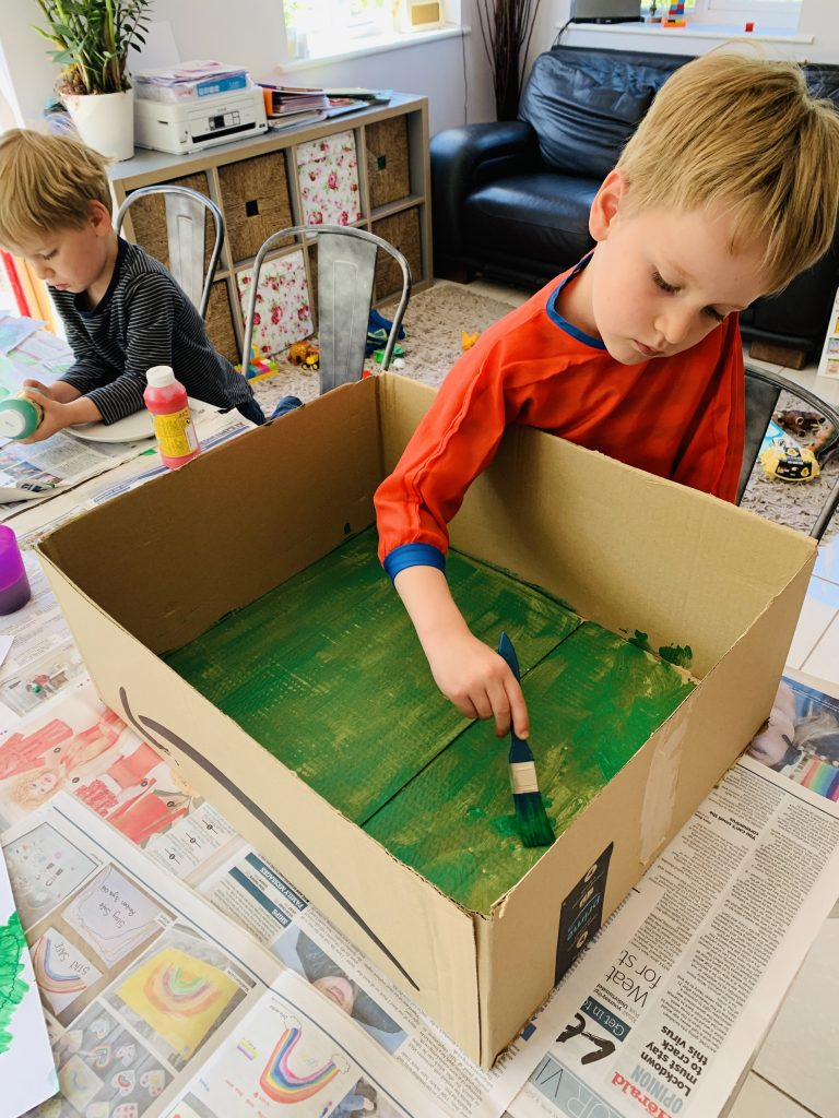 Four year old painting the inside of a cardboard box