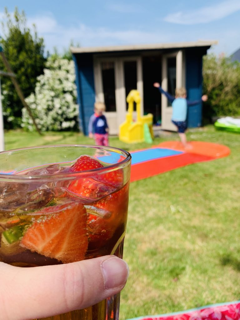Glass of pimms in the garden with children playing on a slip n slide