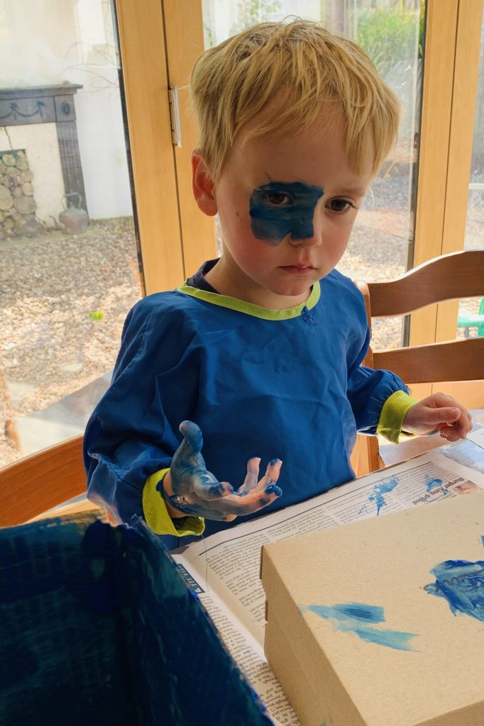 Toddler boy painting his face with blue paint