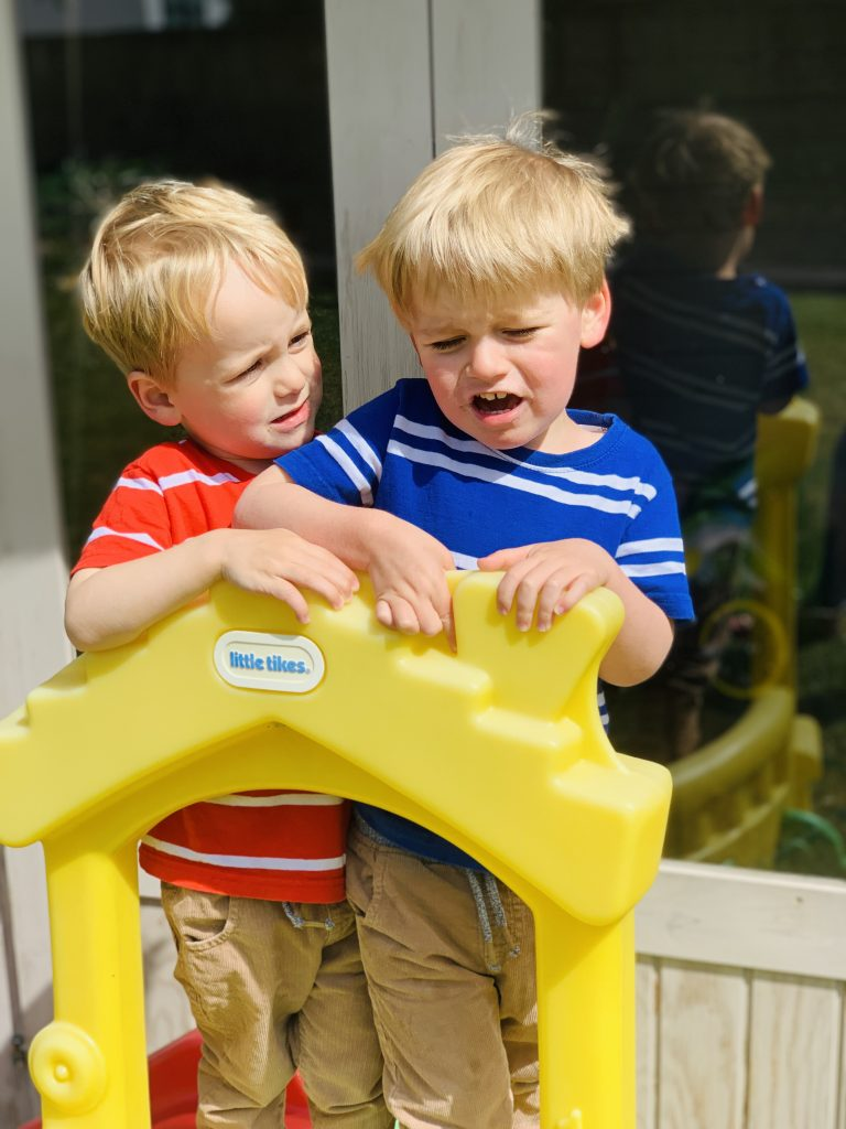 Twins fight over a slide