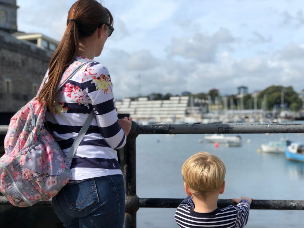 Woman with long brown ponytail and rucksack, wears a stripy top and jeans, and stands overlooking the sea and boats with a little boy wearing a stripy top.