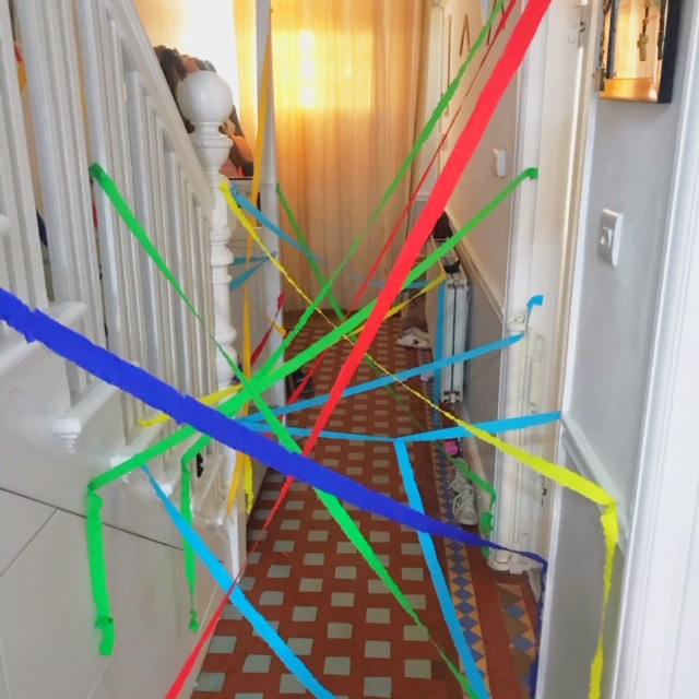 Crepe paper stuck across the hallway for a birthday party at home activity
