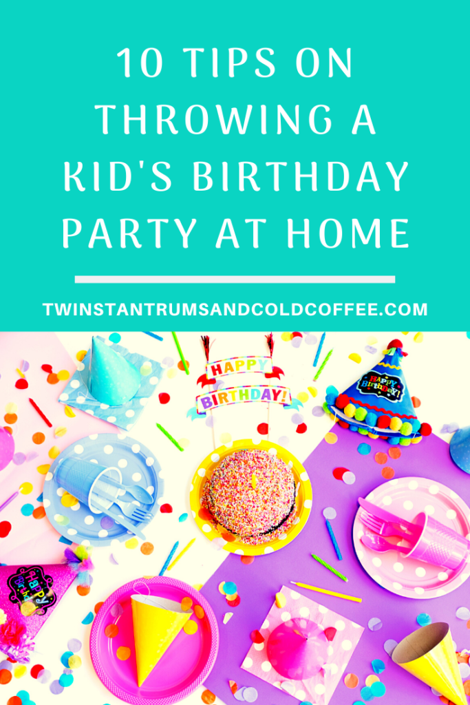 PIN image showing a table laid out for a birthday party at home with cake, party hats and plates