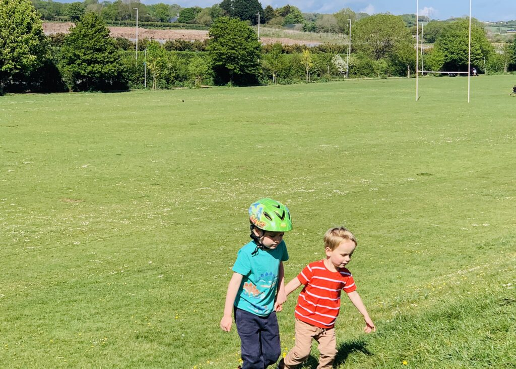 Brothers climbing a slope at King George's Playing Fields one of the great outdoor spaces in Plymouth