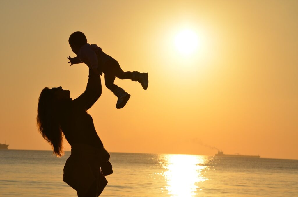 Travel influencer Mum and baby on a beach at sunset