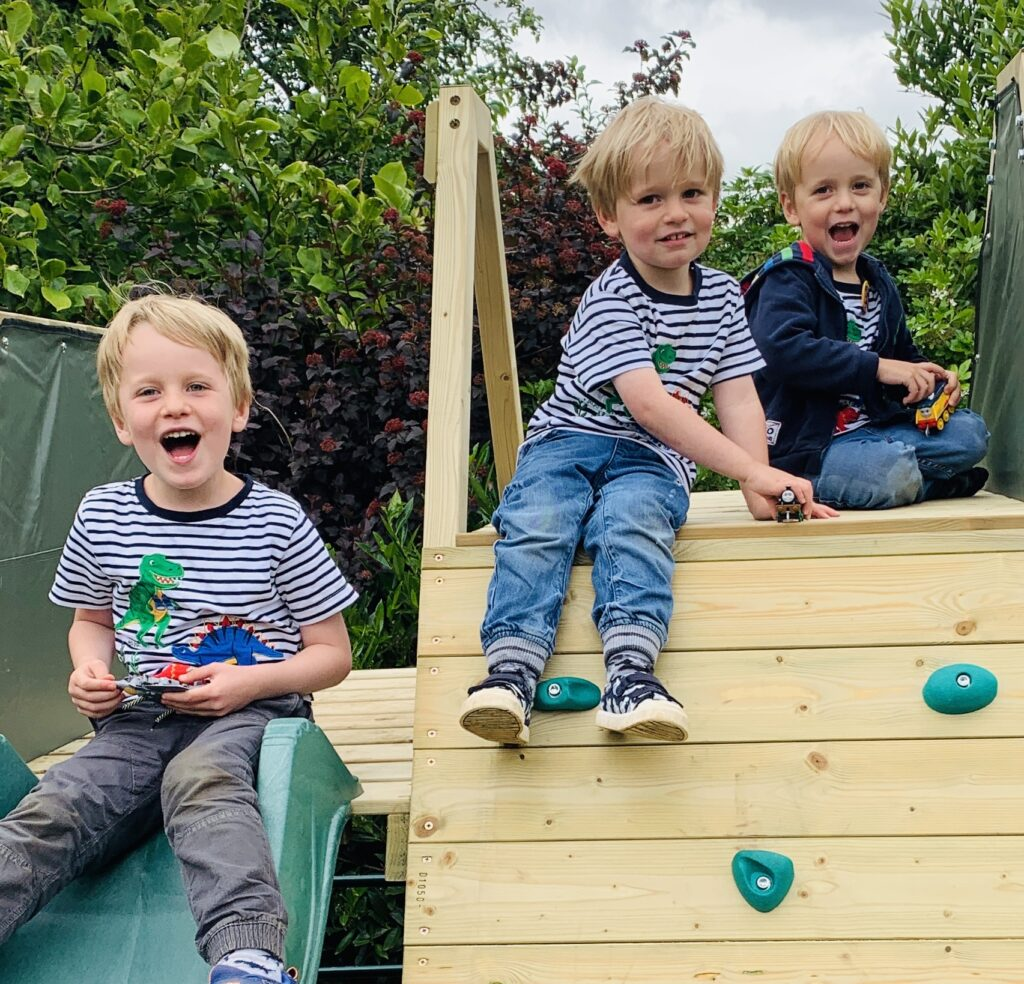 Brothers sitting on a climbing frame in their garden in lockdown