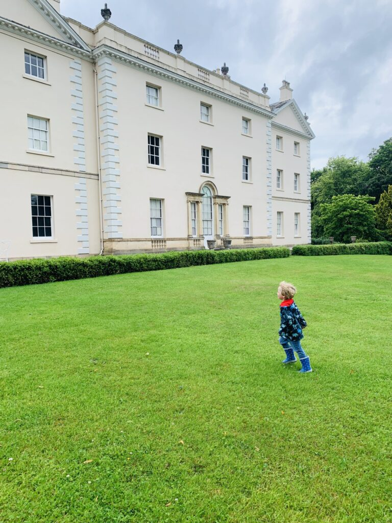 Toddler running on the grass at Saltram House a great idea for things to do indoors in Plymouth with kids