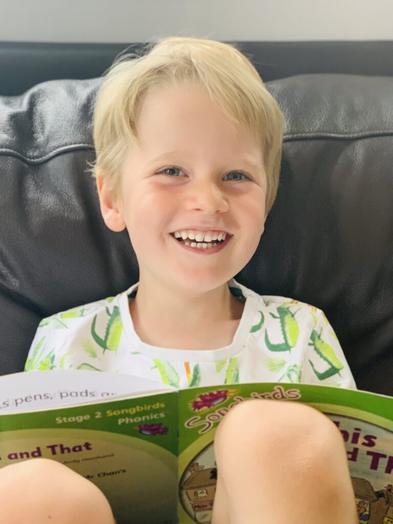 Five year old smiling and reading a school book