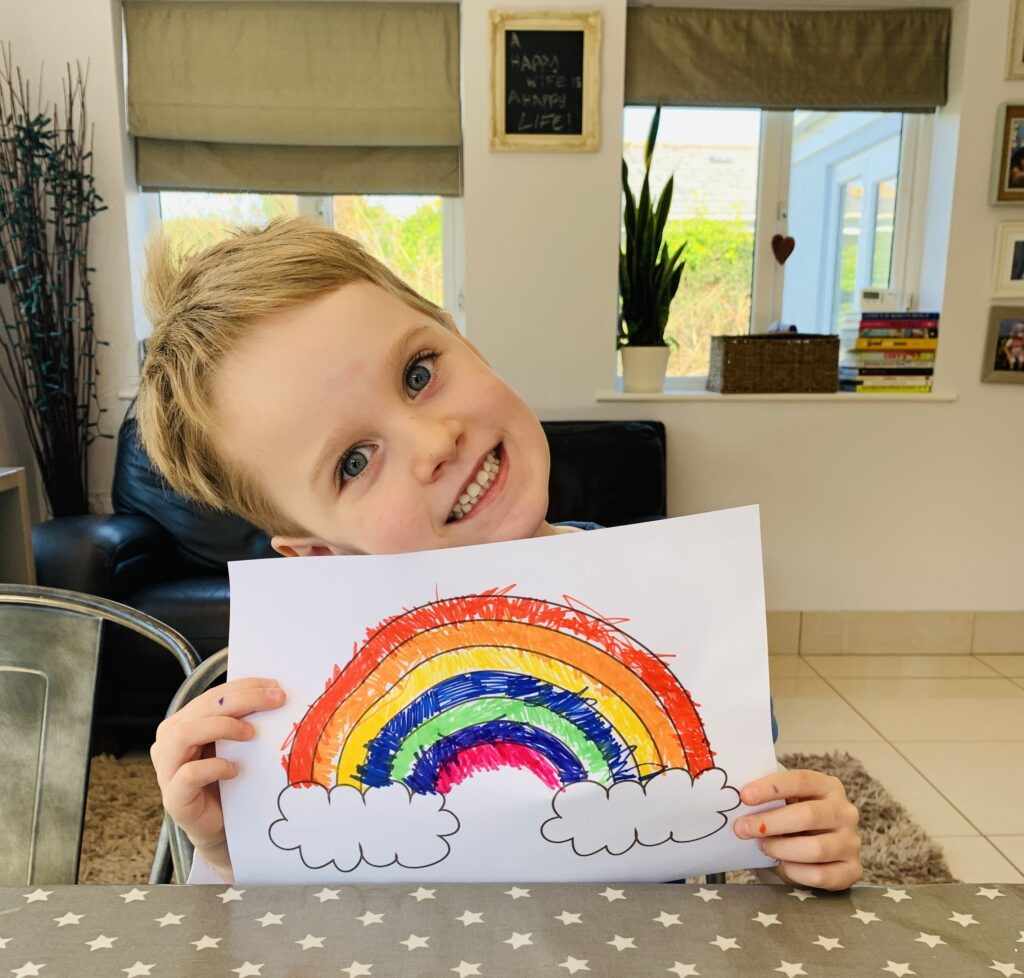 Little boy with the rainbow he's drawn