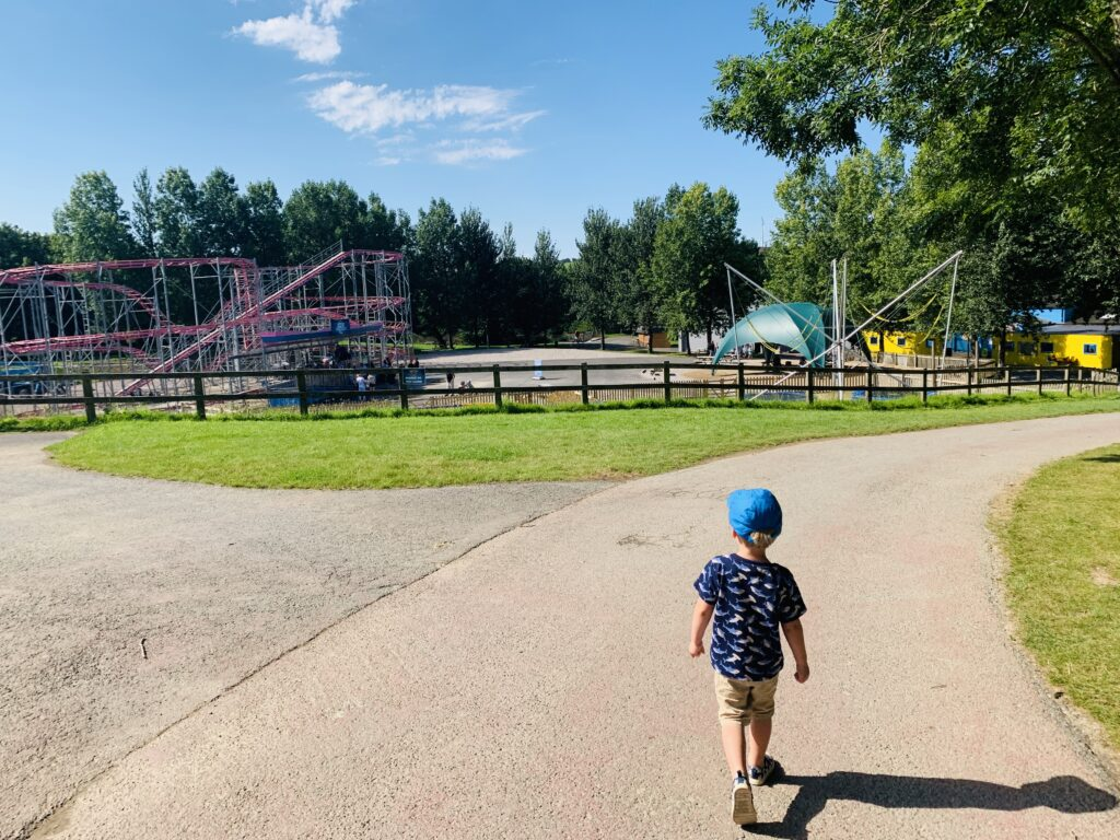 Three year old boy walking through Camel Creek with Air Bender roller coaster in background