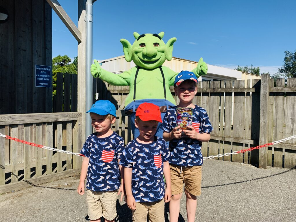 Three year old twin boys and five year old brother in front of Swampy the mascot at Camel Creek