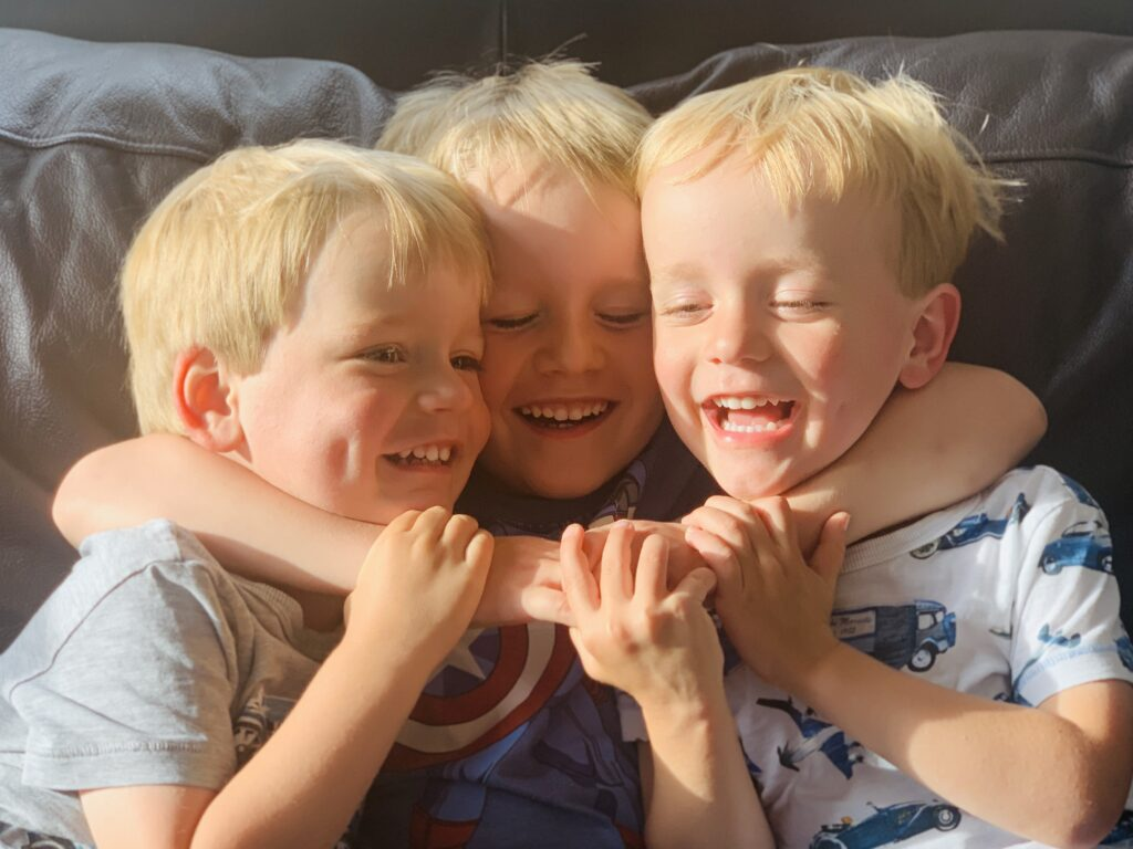 Three year old twins cuddled by five year old brother