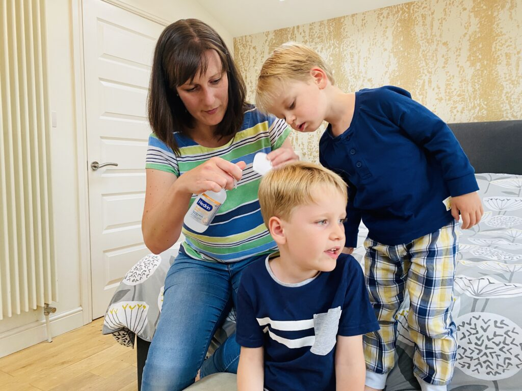 Two year old watches his mum look for head lice in his five year old brother's head