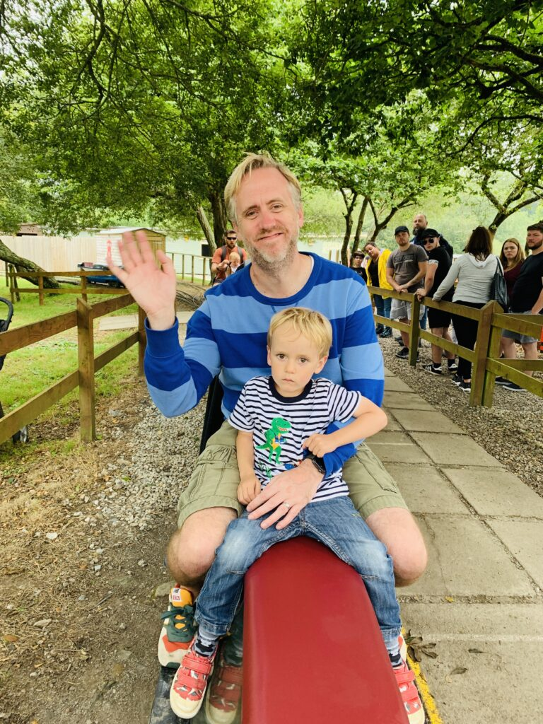 Dad and three year old son on a miniature steam train