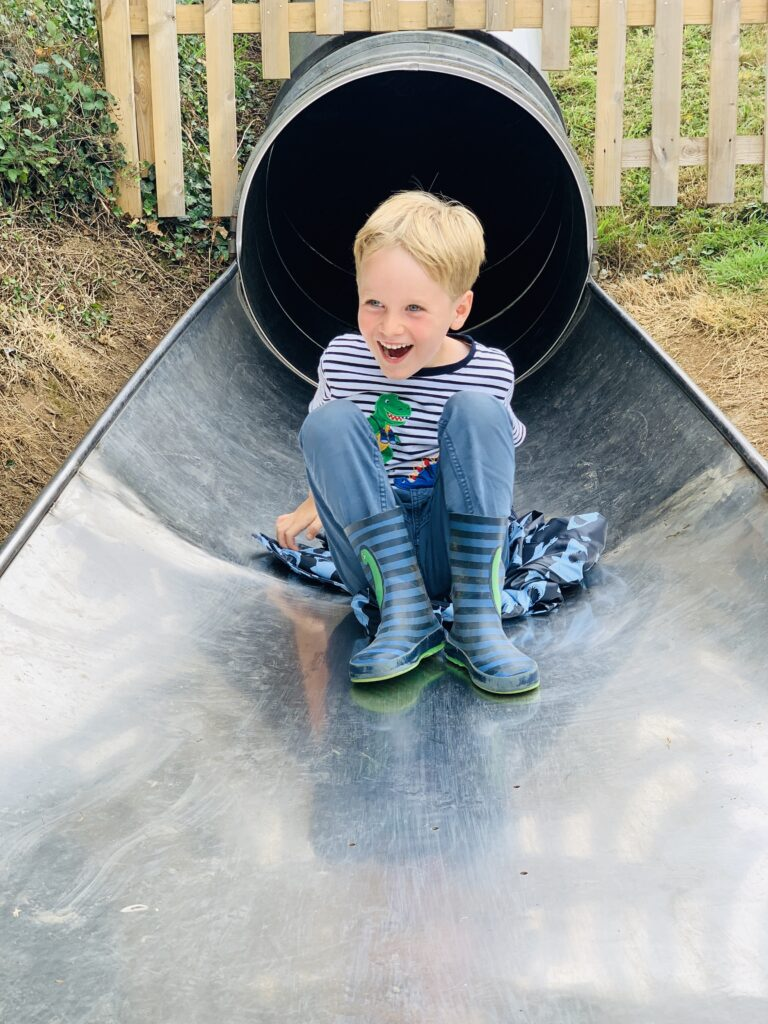 Five year old laughing at the bottom of a tube slide
