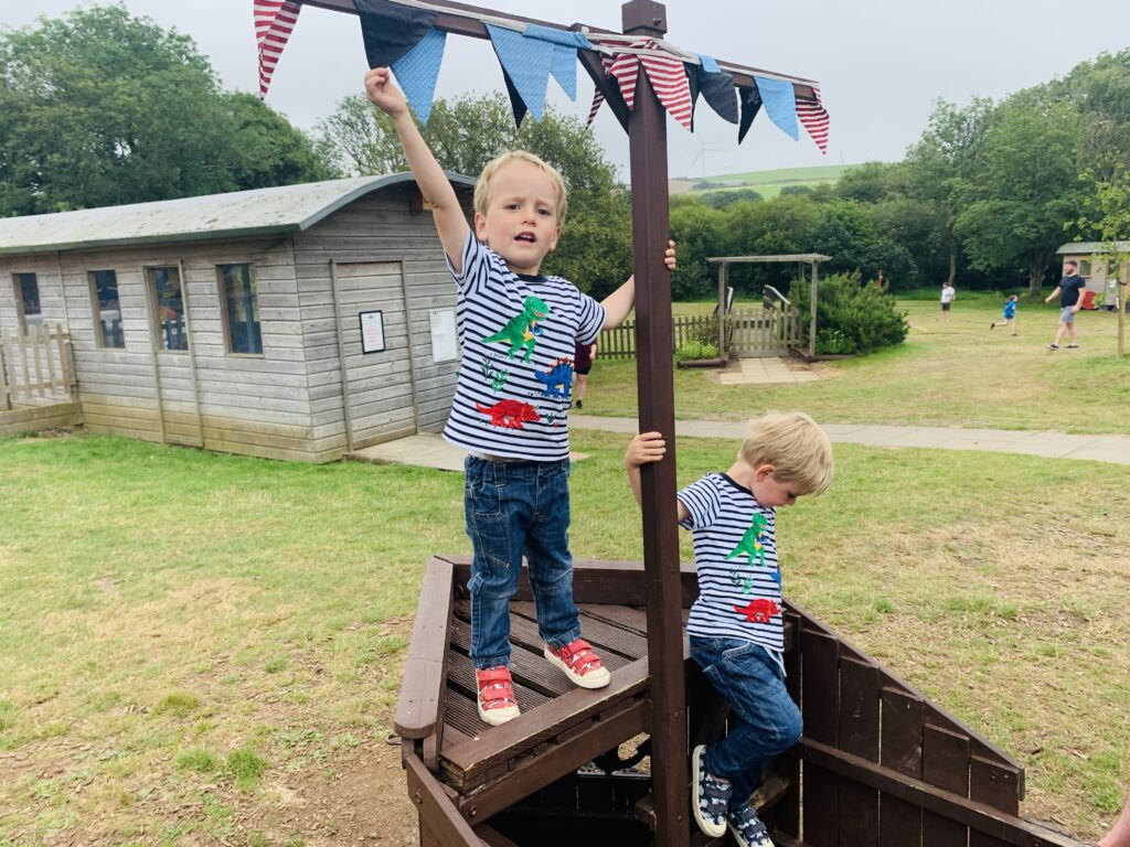 Twin three year old boys playing on a pirate ship at Lappa Valley