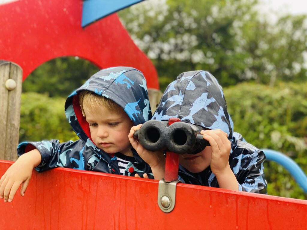 Brothers in rain coats look through some toy binoculars at a park