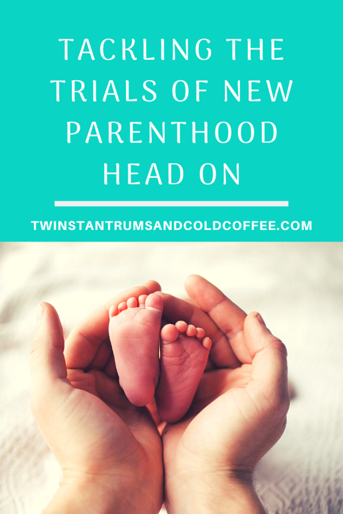 PIN image of parents holding a baby's feet for a post about tackling new parenthood head on