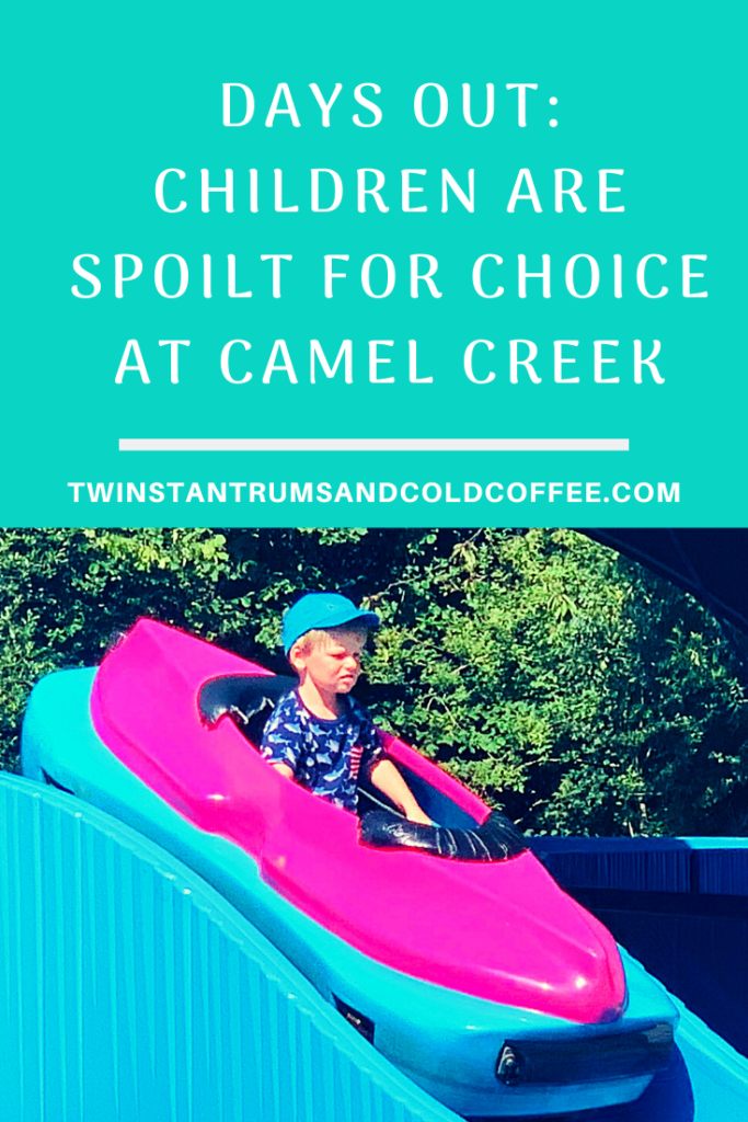 PIN image of a toddler in a mini log flume ride at Camel Creek Adventure Park in Cornwall