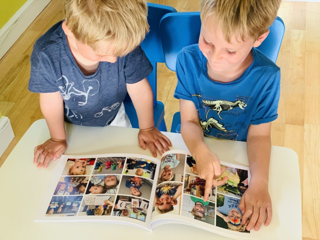 Brothers looking at pictures of themselves in a Rosemood photo book