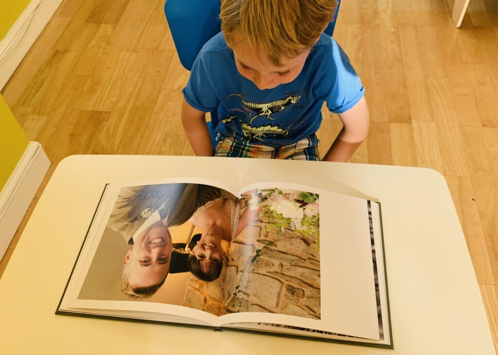 Little boy looking at a wedding picture of his mum and dad in a photo book