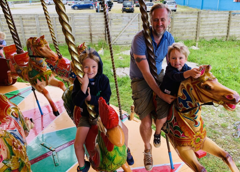Dad and sons on a carousel roundabout